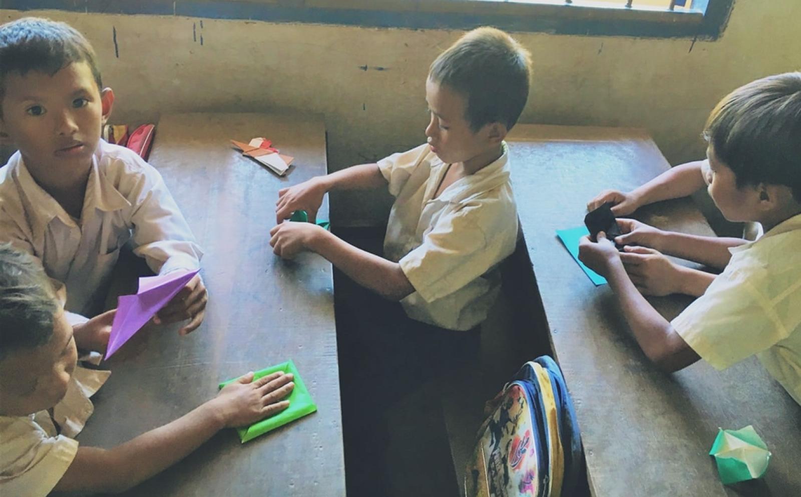 カンボジアの学校で折り紙を一生懸命学ぶ幼い子供たち
